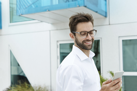 open collar: Smiling man wearing glasses, looking at phone