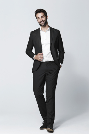 Suited and bearded man smiling in studio