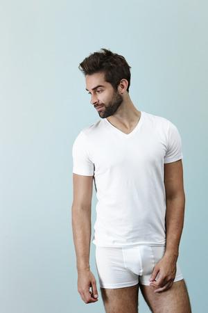 Man in underwear posing in studio, looking away