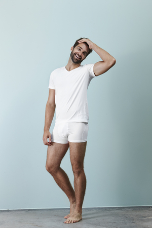 Man laughing in white underwear, portrait Standard-Bild