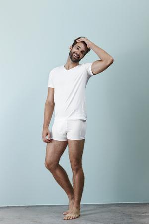 Man laughing in white underwear, portrait Standard-Bild
