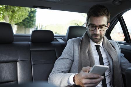 자동차 스마트 폰에서 사업가 문자 메시지 스톡 콘텐츠