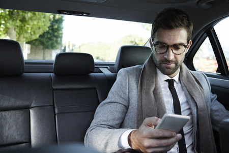 Businessman texting on smartphone in car