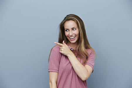 studio model: Beautiful woman in polo shirt, pointing Stock Photo