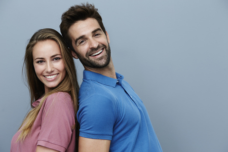 Back to back couple in polo shirts, portrait