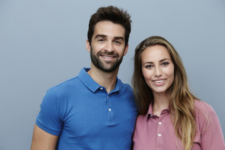 Couple in polo shirts smiling for camera