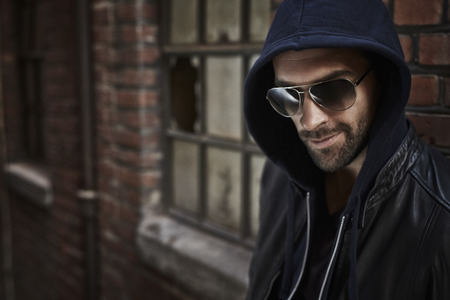 casual hooded top: Street fashion man in sunglasses, looking away Stock Photo