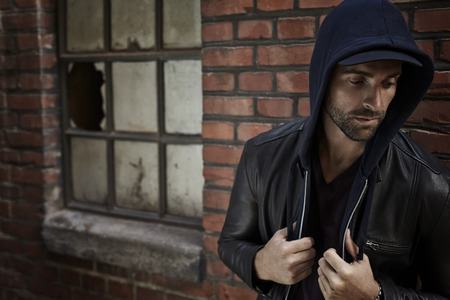 casual hooded top: Hooded and handsome man in street scene Stock Photo