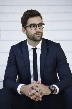three day beard: Businessman in blue suit looking away