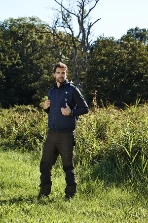 casual hooded top: Hiker guy standing in meadow, portrait