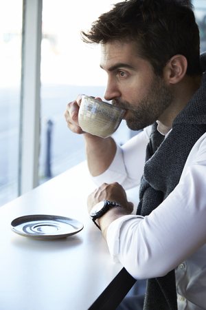 Guy drinking coffee in cafe, looking away