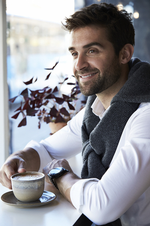 Smiling guy with coffee cup in cafe