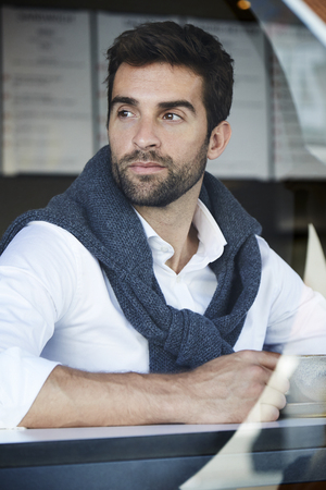 open collar: Handsome man in thought in cafe Stock Photo