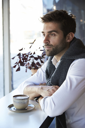 open collar: Thoughtful man with coffee in cafe