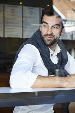 open collar: Man smiling in cafe, looking away Stock Photo