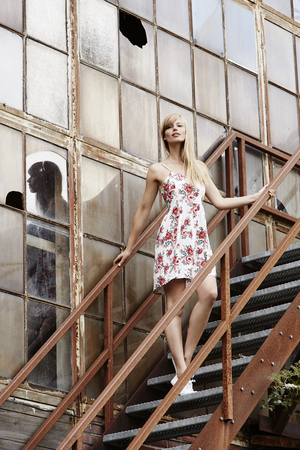Posing beautiful woman on steps of old industrial building