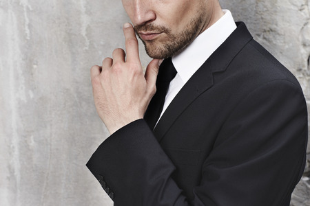 Stubble and suit on sharp dressed man, close up