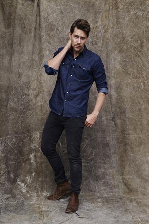 open collar: Posing dude in denim looking at studio Stock Photo