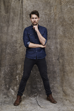 open collar: Man in jeans and shirt posing for camera