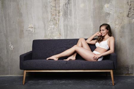 semi dress: Lingerie girl relaxing on sofa, smiling