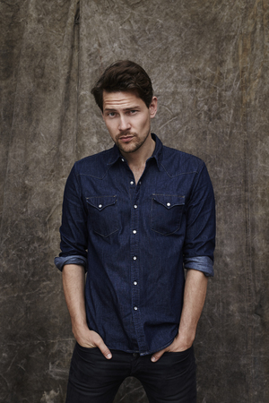 eyebrow raised: Portrait of denim shirt guy, studio Stock Photo