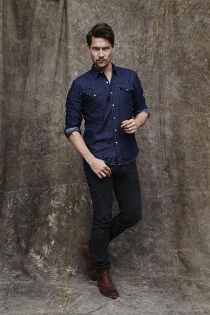 open collar: Portrait of serious man in denim shirt, studio Stock Photo