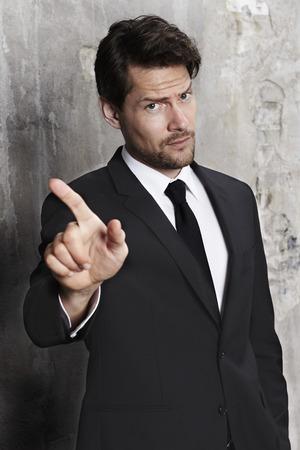 gesturing: Businessman warning by gesturing, portrait