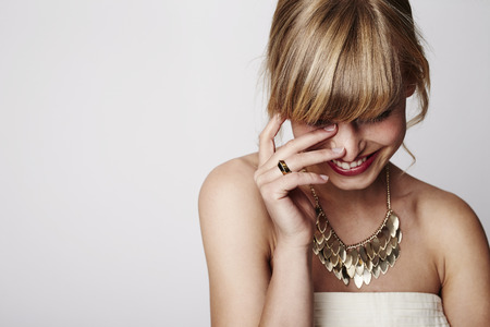 Beautiful blond laughing with gold necklace, close up Standard-Bild