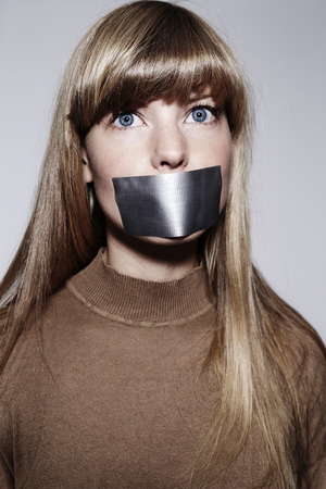 silenced: Blond woman silenced with sticky tape, portrait