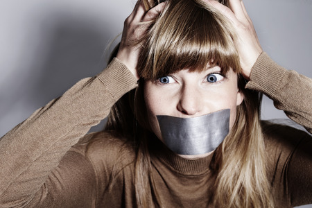 Silent frustration from young woman with taped mouth Stock Photo
