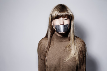 Young blond woman with taped mouth, eyes closed