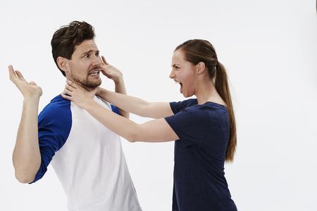 strangling: Woman strangling man in white studio Stock Photo