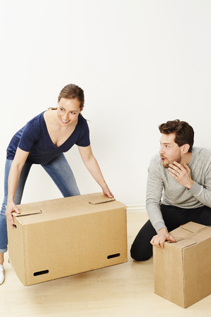 Sleazy dude looking at woman lifting boxes Stock Photo