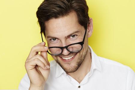 open collar: Man peering over spectacles in yellow studio Stock Photo