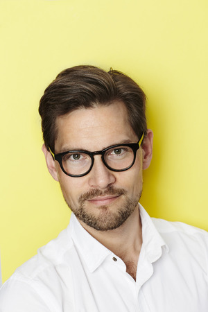 man with a goatee: Portrait of spectacled man in yellow studio Stock Photo