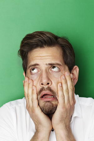 open collar: Man groaning in green studio