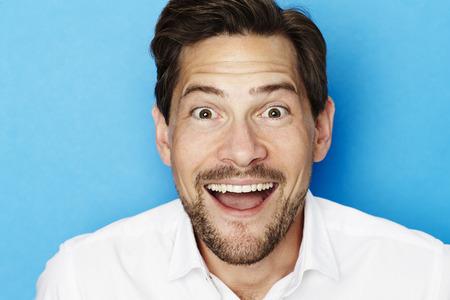 open collar: Portrait of excited guy in blue studio Stock Photo