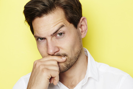 quizzical: Quizzical man raising eyebrow, portrait Stock Photo