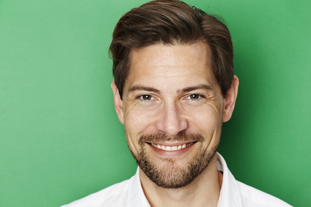 man with a goatee: Portrait of handsome guy against green background