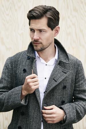 Posing man in grey coat, looking away