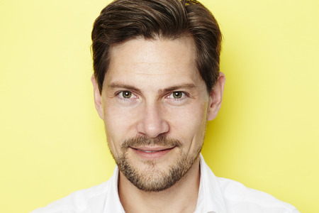 open collar: Goateed man smiling in yellow studio
