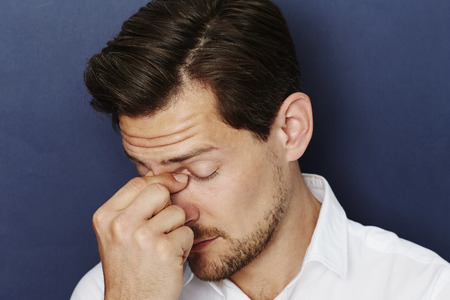 close up eyes: Anxious dude with eyes closed, close up Stock Photo