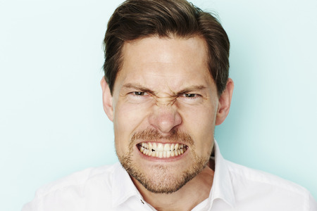 clenching teeth: Angry man clenching teeth at camera Stock Photo