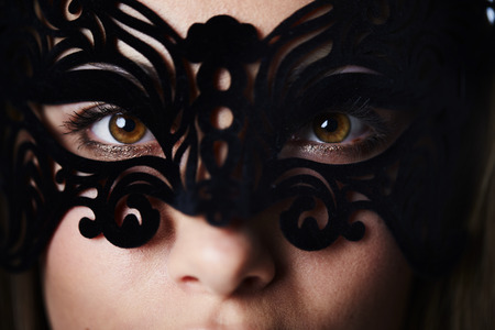 close up eyes: Beautiful and masked woman with brown eyes, close up Stock Photo