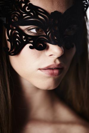 Beautiful woman in ornate mask, looking away