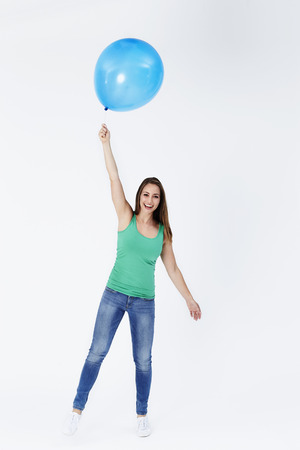 Portrait of young woman floating with balloon Stock Photo
