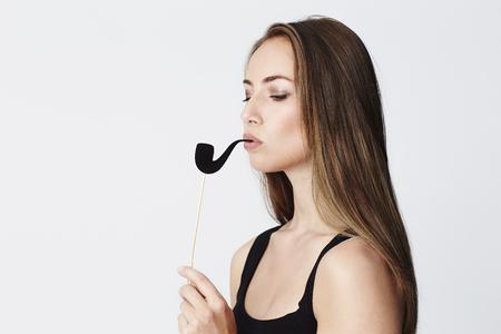 messing: Beautiful woman smokes play pipe, studio