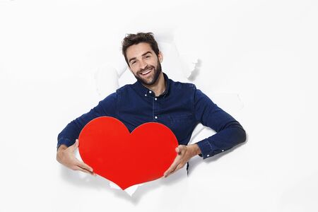 Passionate man with love heart emerging from page