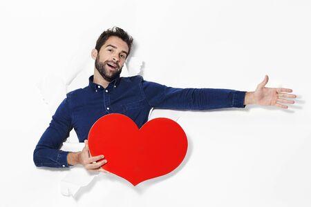 Man declaring love with heart in studio