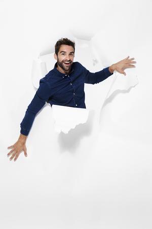 Man emerging through torn paper in studio, portrait